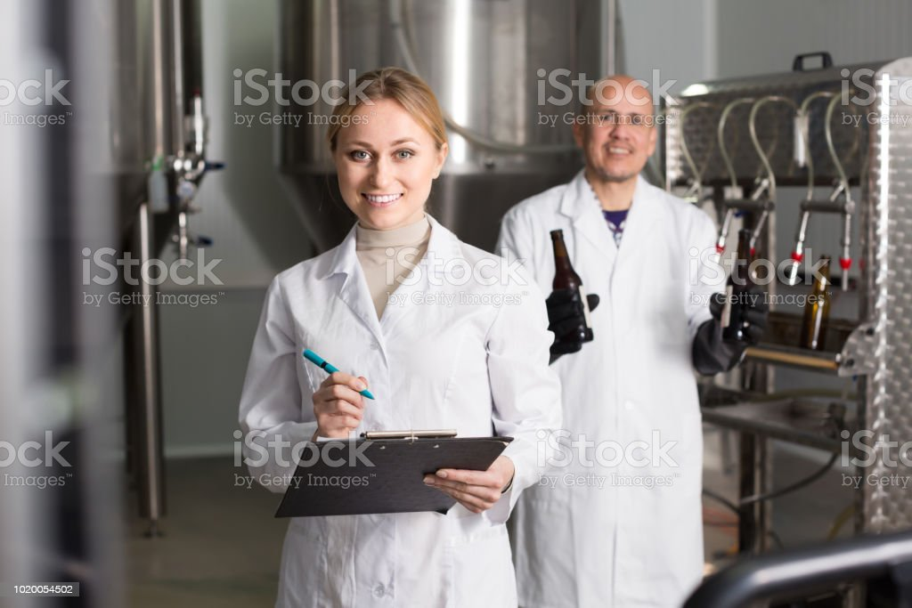 Woman and man in modern beer production facility stock photo
