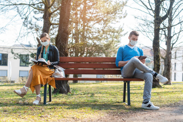 Woman and man in social distancing sitting on bench stock photo