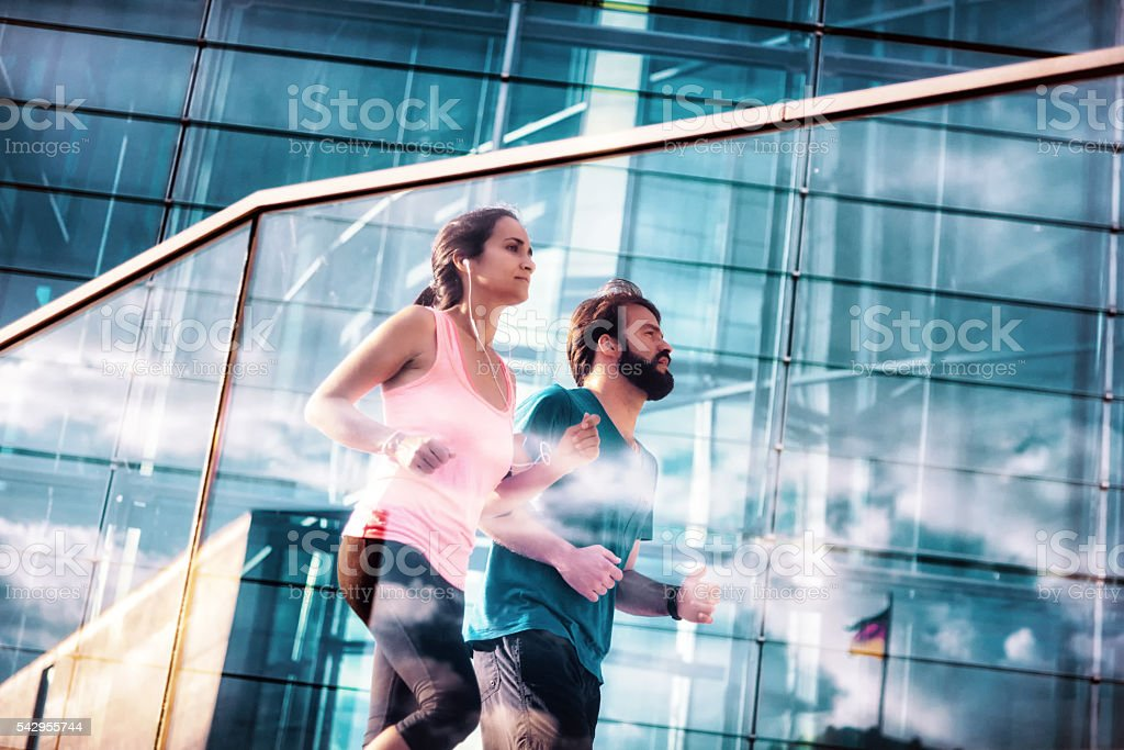 woman and man jogging in modern business district in berlin stock photo