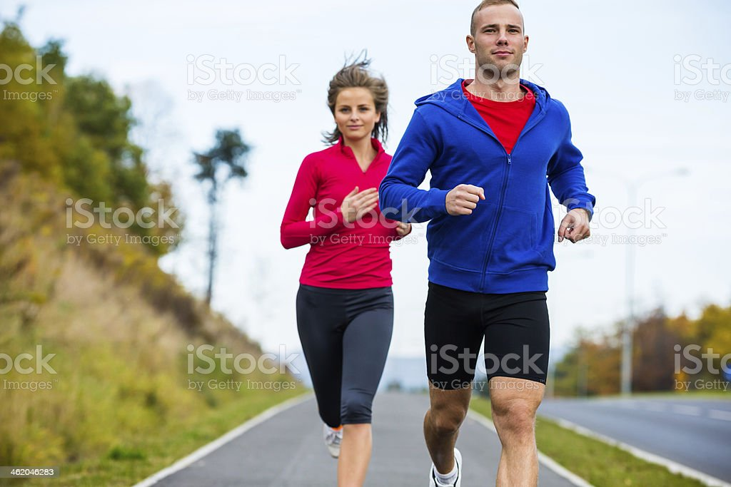 Woman and man jogging stock photo