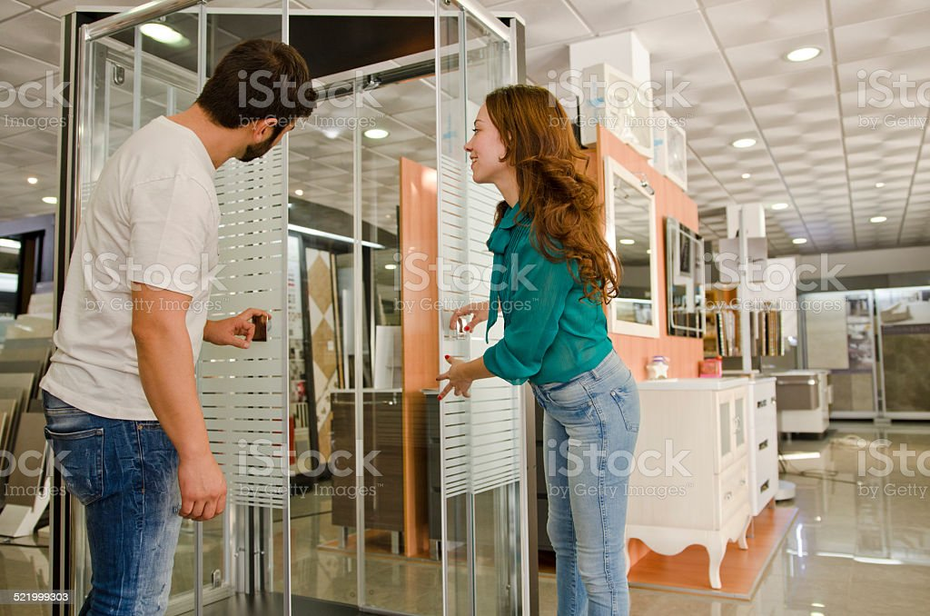 Woman and man looking shower enclosures stock photo