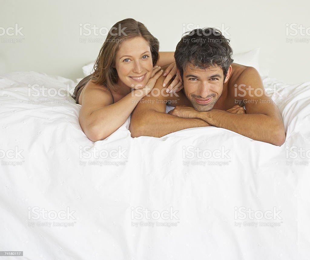 Mulher e o homem deitado na cama foto de stock royalty-free