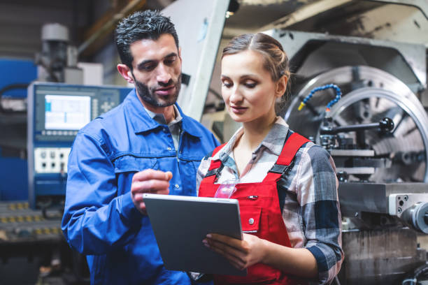 Woman and man manufacturing worker in discussion stock photo