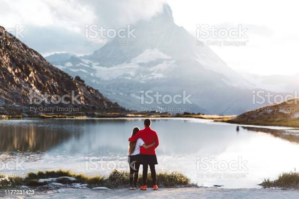 Photo of Woman and man meet sunset at the beautiful mountain lake in Swiss Alps