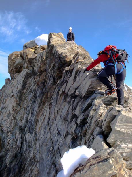 Frau und Mann Bergsteiger auf dem Weg zu einer hohen Bergspitze entlang einem schmalen Felsgrat – Foto