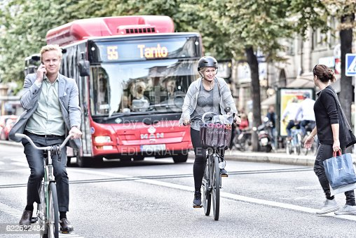 583973114istockphoto Woman and man on bicycles in traffic, bus in background 622522484