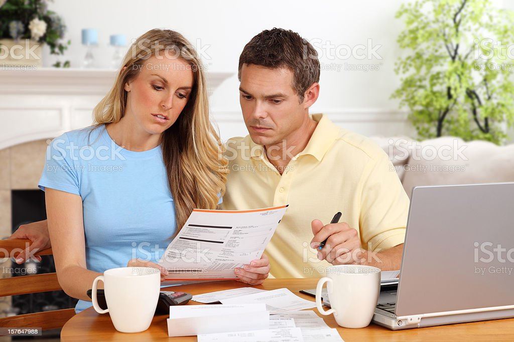 A woman and man paying their paper bills on their laptop royalty-free stock photo