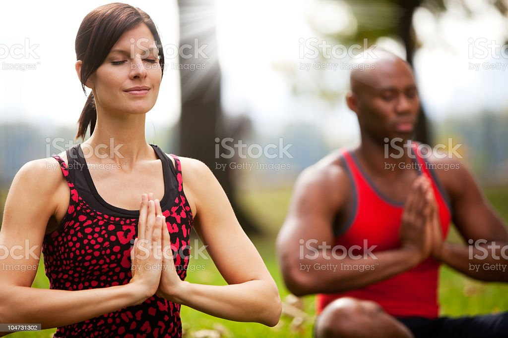 Woman and man peacefully meditating outdoors royalty-free stock photo