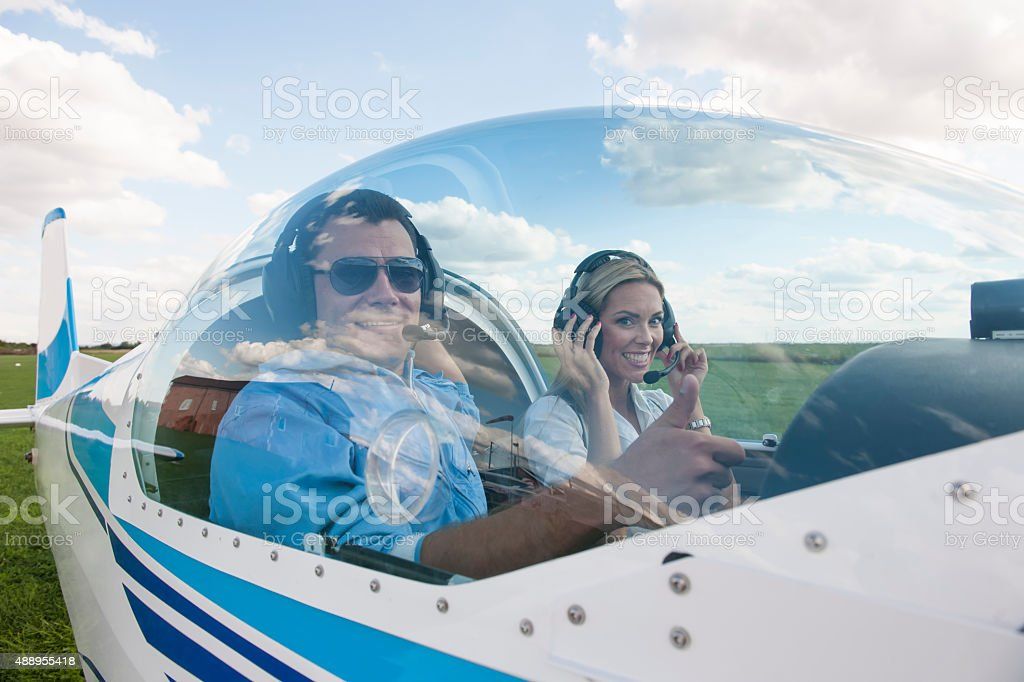 Woman and man pilot looking at camera, preparing for flying stock photo