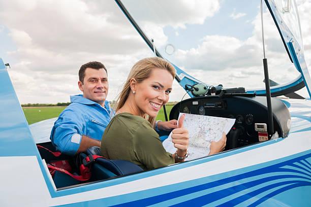 frau und mann pilot blick auf karte, die vorbereitung für flying - flugschule stock-fotos und bilder