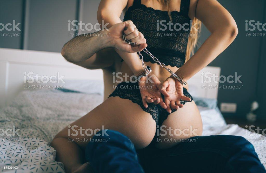 Juegos de dominación en la cama hombre y mujer foto de stock libre de derechos