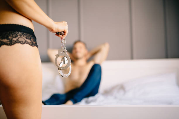 woman and man playing domination games in bed - man dominating woman stock photos and pictures
