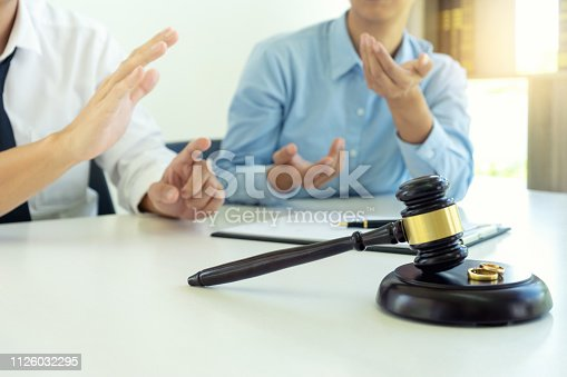 istock woman and man quarrel in front of gavel 1126032295