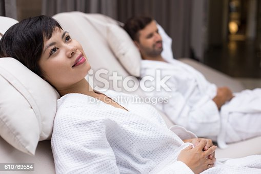610769340istockphoto Woman and Man Relaxing on Loungers after Spa 610769584