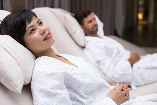 610769340 istock photo Woman and Man Relaxing on Loungers after Spa 610769584