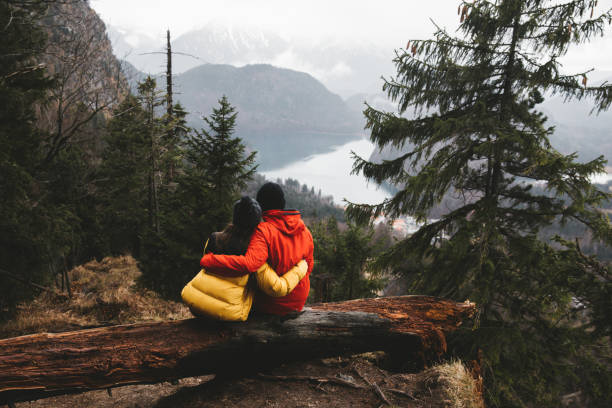 Woman and man sit in the forest hugging and looking at Bavarian Alps landscape stock photo