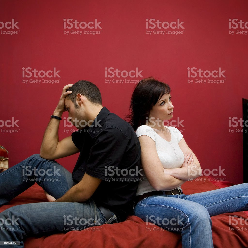 Woman and man sitting back to back on bed  royalty-free stock photo