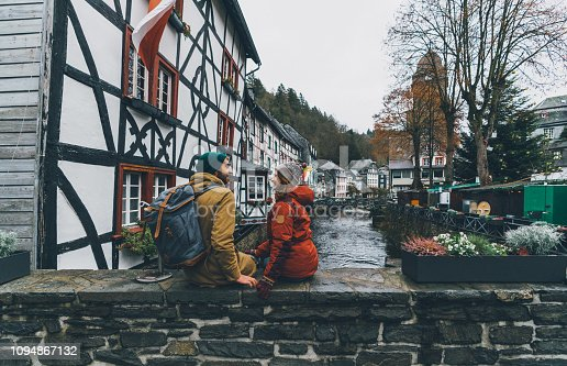 Young Caucasian woman and man sitting on bridge and looking at Old town of Monschau in Germany