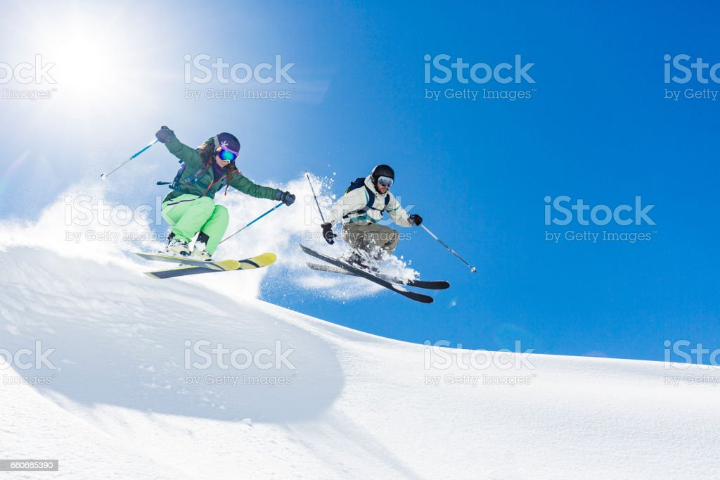 Woman and man skiing and jumping stock photo