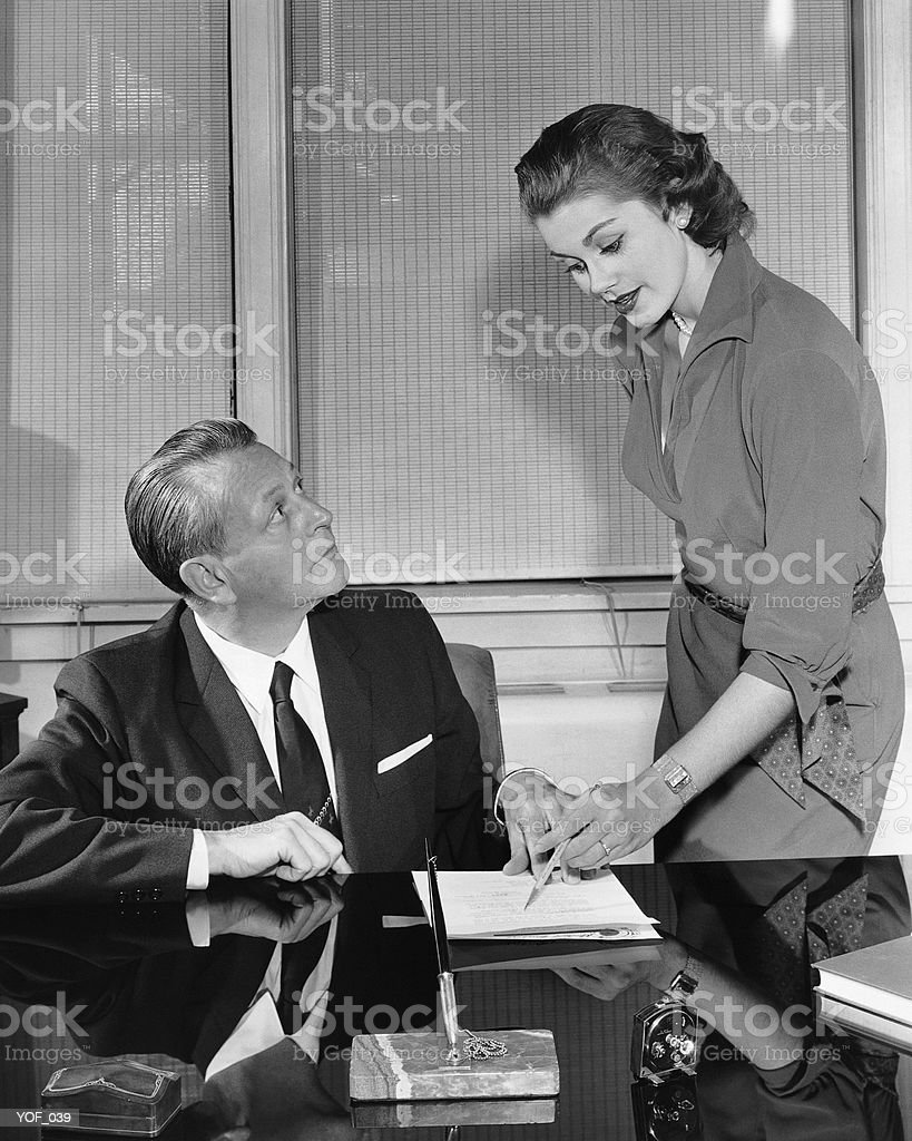 Woman and man talking and pointing to paper royalty-free stock photo
