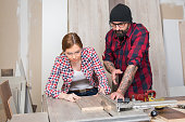 Woman using power tools in a carpenter workshop, man teaching her how to work, equality