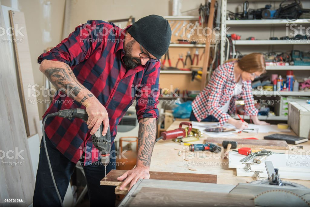 Woman and man using power tools in a carpenter workshop – Foto