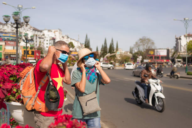 Woman and man wearing sanitary mask outdoors in Da Lat city centre Vietnam. Medical mask protection against risk of chinese flu virus epidemy in Asia. Anti smog mask traffic pollution. stock photo