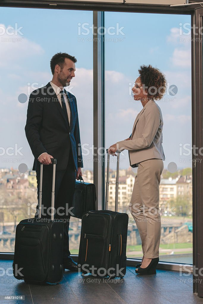 Woman and man with suitcases in hotel hall Afro amercian businesswoman and caucasian businessman in formal outfits on business travel, talking in hotel hall by the window, holding suitcases.  2015 Stock Photo