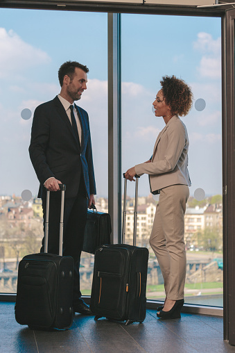 Woman And Man With Suitcases In Hotel Hall Stock Photo - Download Image Now