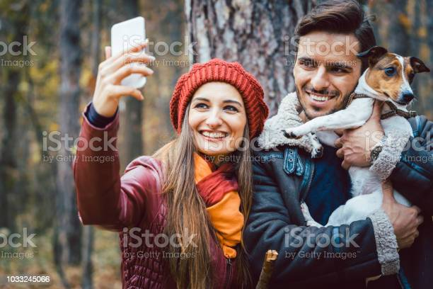 Woman and man with their dog on autumn walk taking a phone selfie picture id1033245066?b=1&k=6&m=1033245066&s=612x612&h=2ujnk3zwruci7i1tpgc8hjc3nhbnxkcrs6pmxyztde4=