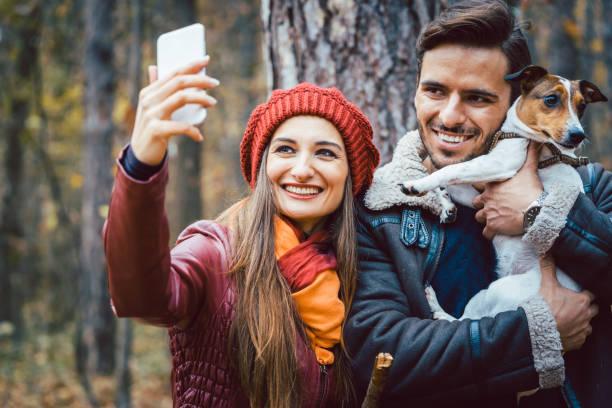 Frau und Mann mit ihrem Hund auf herbstlichen Spaziergang unter Telefon selfie – Foto