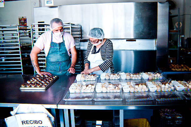 woman and man working at bakery workshop - mexikanisch kochen stock-fotos und bilder