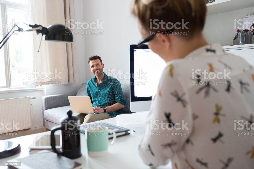 Woman and man working in an office Woman and man working in an office. Focus on man sitting on sofa and using a laptop. In the foreground defocused woman working at the desk.  2015 Stock Photo