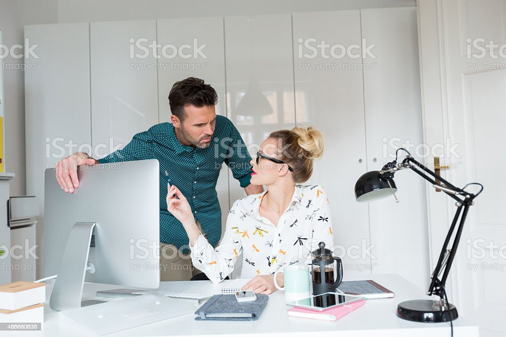 Woman and man working in an office Blonde woman sitting at the desk in an office and talking with her colleague. 2015 Stock Photo
