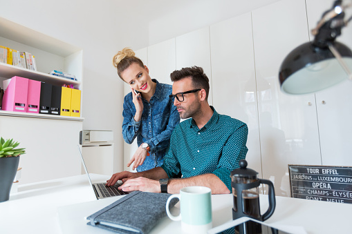 Woman And Man Working Together On Laptop In An Office Stock Photo - Download Image Now