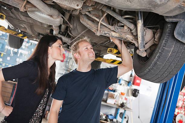 Woman and mechanic looking at car repairs stock photo