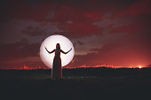 Young woman silhouette and moon. Light painting.