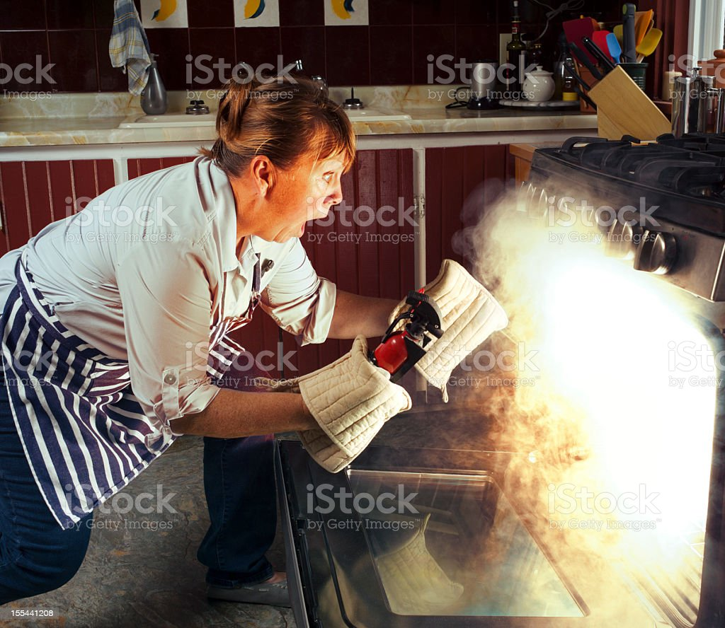 Woman and Oven Fire While Cooking in the Kitchen stock photo