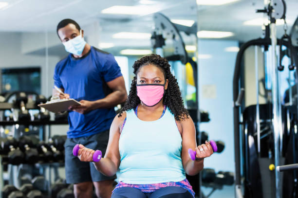 Woman and personal trainer in gym, wearing masks stock photo