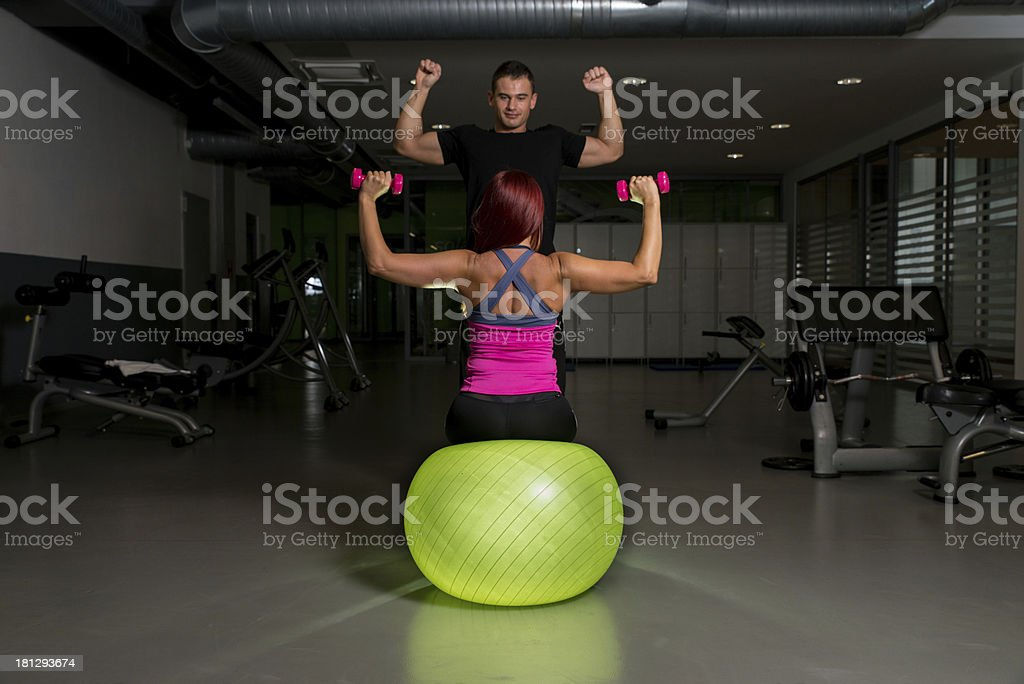Woman and Personal Trainer in gym with dumbbells royalty-free stock photo