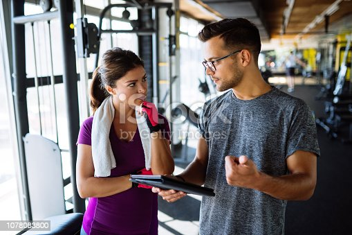 860045834istockphoto Woman and personal trainer making exercise plan in gym 1078083800