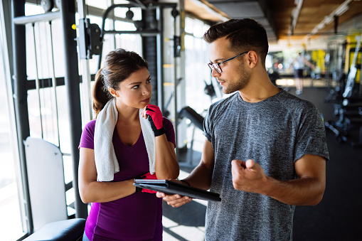 860045834 istock photo Woman and personal trainer making exercise plan in gym 1078083800