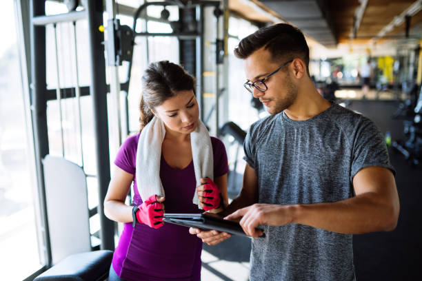 Woman and personal trainer making exercise plan in gym stock photo