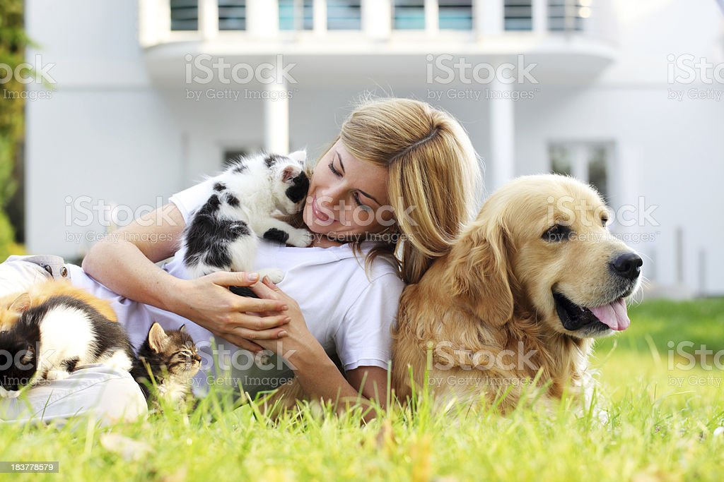 Woman and pets resting on the green garden royalty-free stock photo