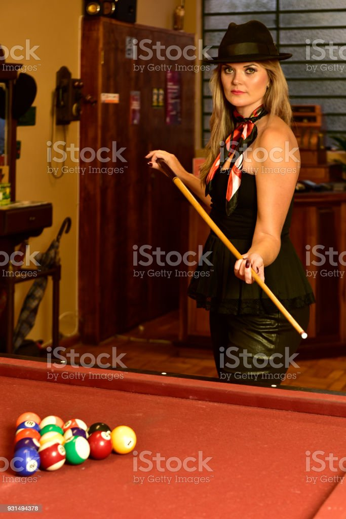 Blonde woman with a hat holding a club next to a pool table