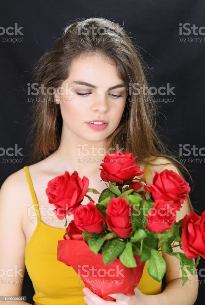 A beautiful young woman receives red roses for a special occasion.
