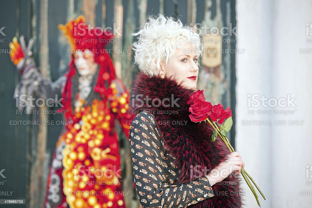 Beautiful woman with a red and black outfit, holding roses for the...