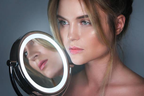 frau und rundspiegel mit led-licht - haarschnitt rundes gesicht stock-fotos und bilder