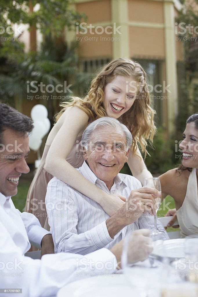 Woman and senior man at outdoor party being affectionate and smiling royalty-free stock photo