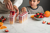 istock Woman and son making orange and strawberry ice pops 1318427091